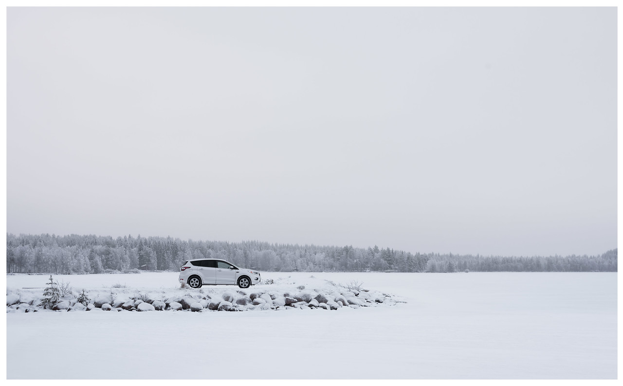 A Ford Kuga stands alone by a frozen lake in a very high-key, minimal and snowy landscape.
