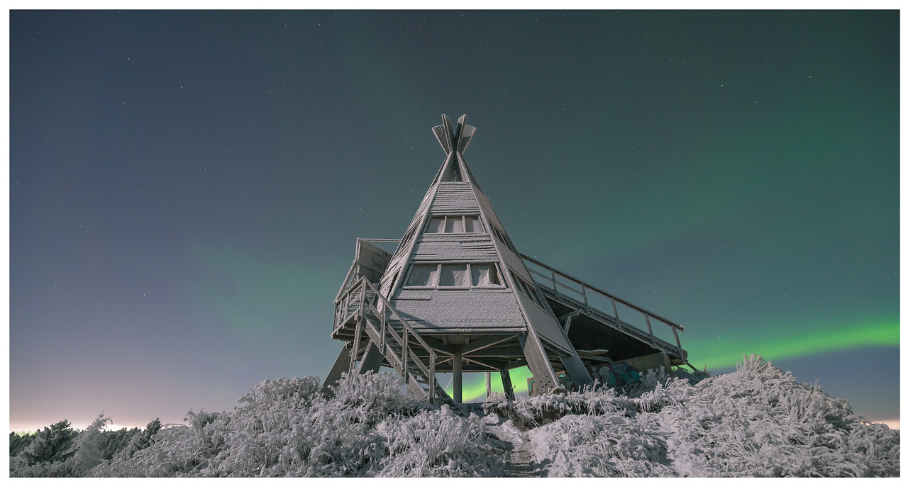 The northern lights (aurora borealis) behind a snow-covered wooden teepee in Arctic Finland.