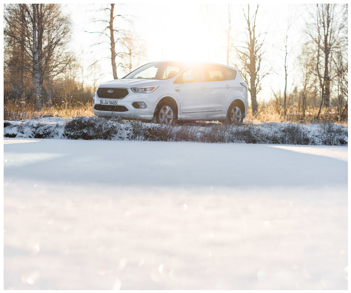 A Ford Kuga parked by a Frozen lake in Finland with the sun behind it.