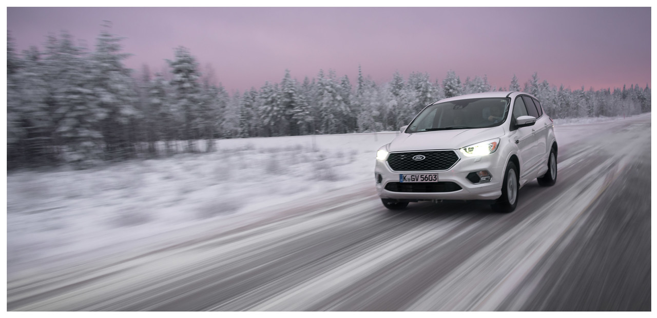 A Ford Kuga with motion blur travelling down an Arctic road at sunrise in Finland.