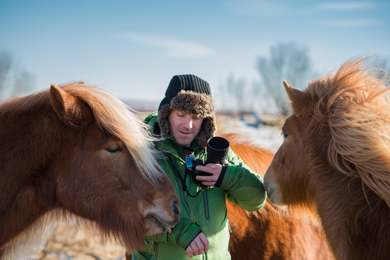 Photography of Conor surrounded by horses in Iceland.